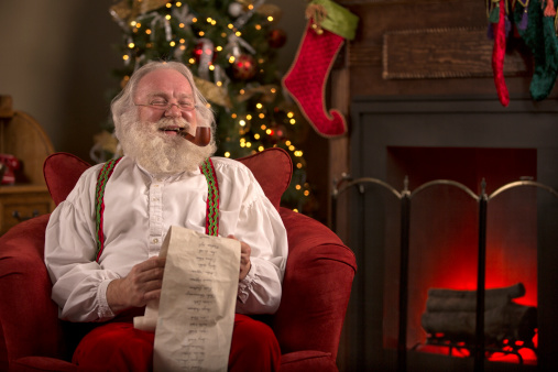 22/12 Volutes dominicale.... Santa-claus-sitting-at-home-smoking-a-pipe-reading-list-picture-id505482987.jpg?u=http%3A%2F%2Fmedia.gettyimages